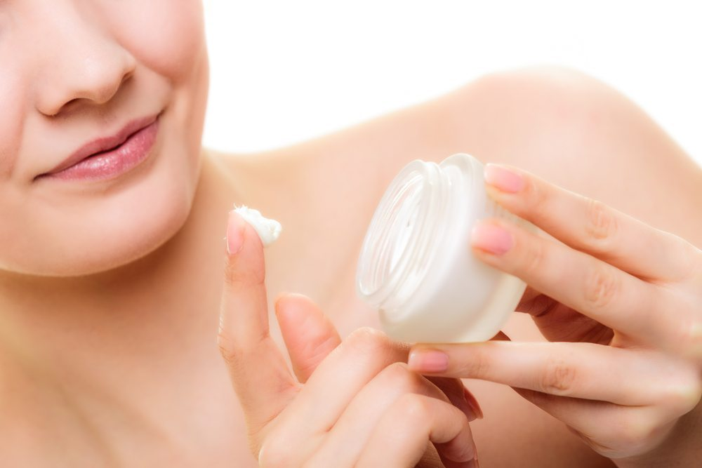 Woman treating her dry skin with moisturizer
